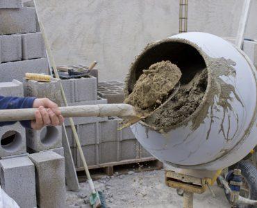 Un homme qui rempli la bétonnière de sable
